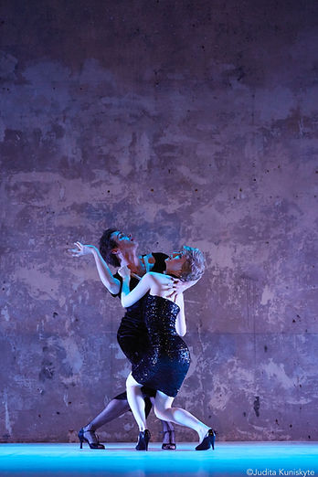 Two dancers in black dresses intertwined and looking upward. Behind them is a large distressed wall and they are on a blue lit floor.