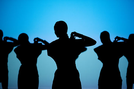 Five dancers in sillouette against a blue background with both hands purched on their right shoulders