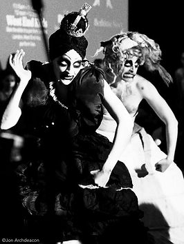 Two dancers, one in white and one in black in a black and white photograph pulling funny and scary faces. They are in the same pose with their right hand near to their shoulder and left hooked low.