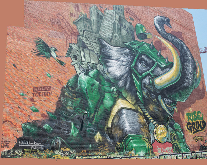 """""""Rise & Grind"""" mural showcasing Stomper, the A's mascot, as a war elephant carrying Oakland on his back. Oakland's largest mural measuring @ 100'x100'."""