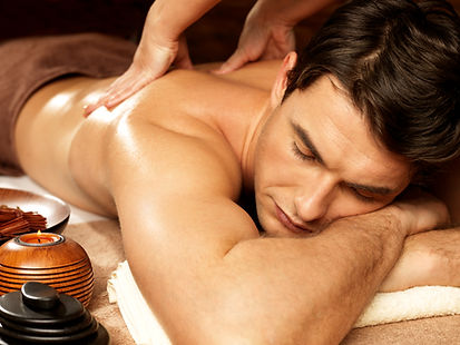 Masseur doing back massage on man body i