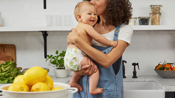 Postpartum mom holding baby in the kitchen kissing smiling baby's head. You can feel better after counseling for moms st. louis, mo and online therapy for women in missouri at Marble Wellness!