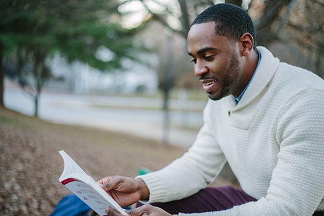 Man reading book outside smiling. He is reading up on how some skills to deal with his mental health. Marble Wellness offers therapy for men in st.louis. You can reclaim your life with counseling for men. Get in touch today!
