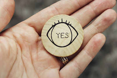 """Hand holding a wooden coin with an eye and the word """"Yes"""" on it. You can get online therapy in missouri from a STL therapist here."""