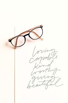 """Glasses on a piece of paper with the words """"Loving. Capable. Kind. Worthy. Giving. Beautiful."""" written. Anxiety, stress and worry can be addressed in counseling in St. Louis at Marble Wellness. Online therapy in Missouri can help with your anxiety and stress too!"""