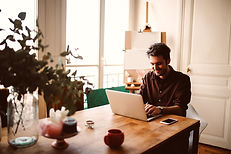 Man at a table at home doing online therapy in Missouri with a licensed online therapist in Missouri. St. Louis based Marble Wellness provides online counseling in Missouri for depression, anxiety, mothers, and more.