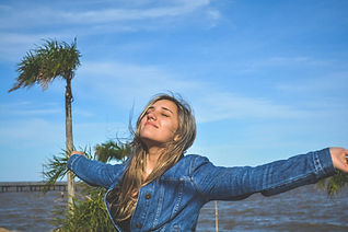 """Young woman at the beach, feeling better and smiling after counseling for chronic illness in St. Louis, MO or via online therapy in Missouri and online therapy in Illniois. You can get options for a """"chronic illness counselor near me"""" for therapy for chronic pain, anxiety, and more."""