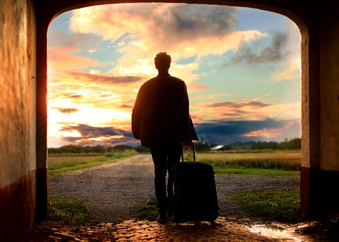 Person with a suitcase walking out on to the road into the sunset. Anxiety, stress and worry can be addressed in counseling in St. Louis at Marble Wellness. Online therapy in Missouri can help with your anxiety and stress too!