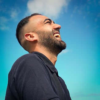 Happy man smiling and looking up in the sun after therapy for men in St. Louis, MO with Marble Wellness. You can get help with online therapy in missouri and counseling for men in STL. Find relief today with online counseling in missouri.