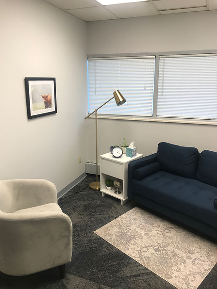 Inside of a therapy office in Ballwin, MO. There is a chair and couch with rug, lamp and table with tissues and a clock ready for therapy in West County, Missouri. You can even get walk and talk therapy in Kirkwood, MO with a west county therapist for anxiety, depression, maternal overwhelm and more with an STL therapist.