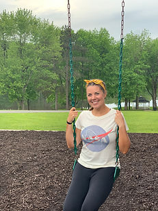 St. Louis therapist, Stephanie, sits on a swing in the park smiling at the camera. Join this missouri counselor for park sessions or walking therapy for a walk and talk in Forest Park. Or, online therapy in Missouri for moms and maternal overwhelm during postpartum and for moms of teens.