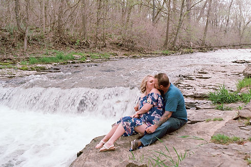 Couple kissing in front of a waterfall.