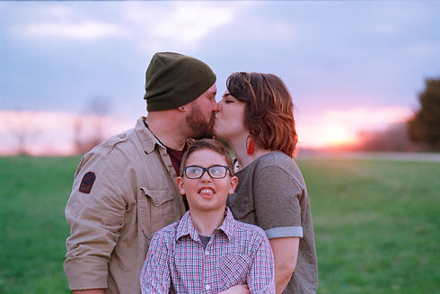 Family photo.  Mom and dad kissing, young son making funny face.