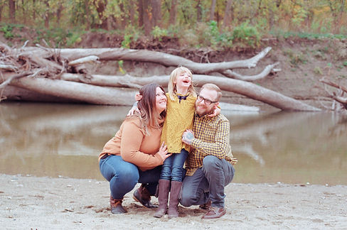 Family laughing in front of water