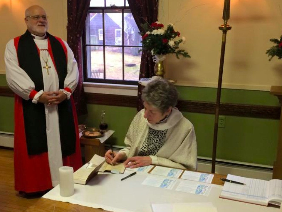 Bishop Katharine Jefforts Schori, signing prayerbooks.