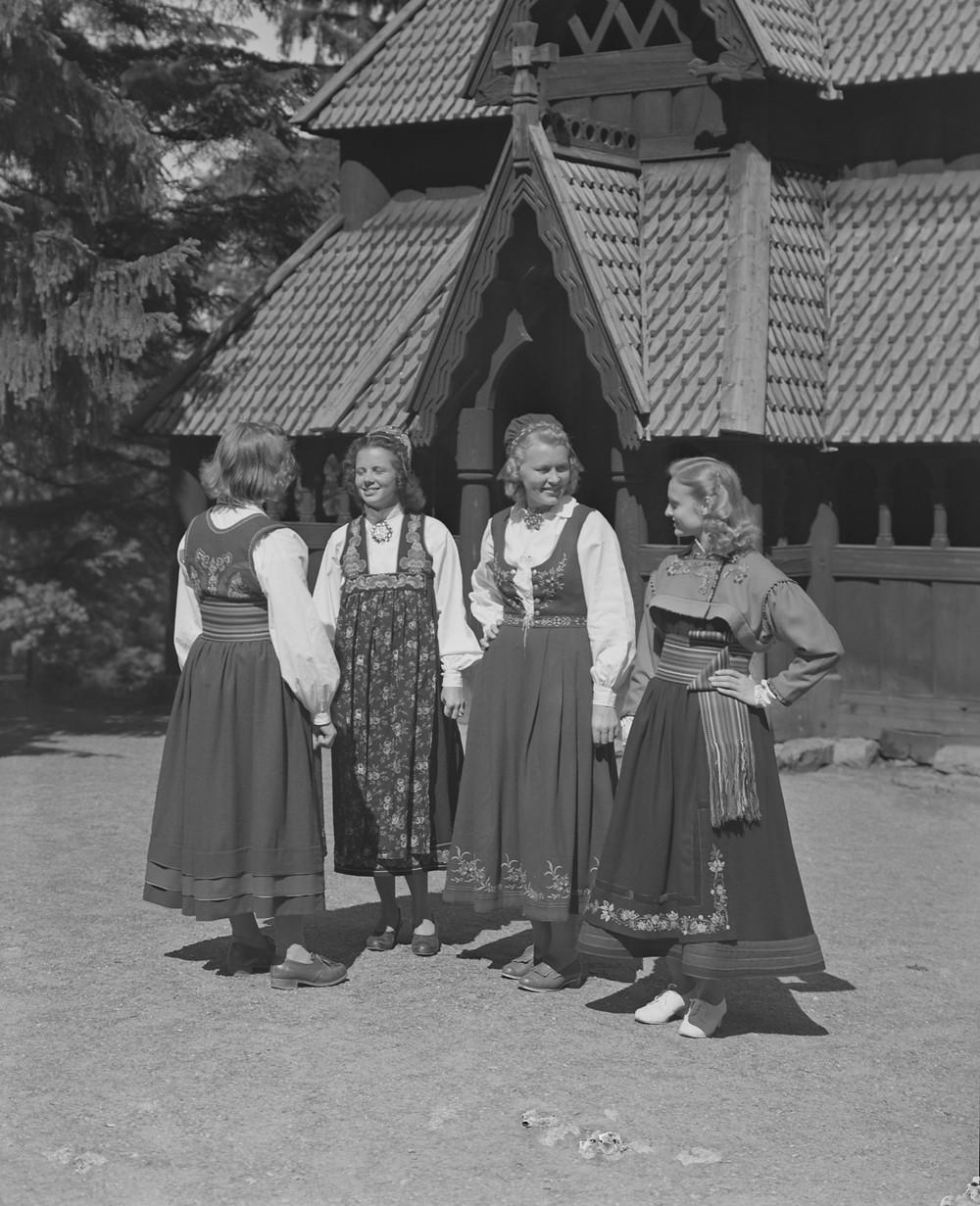 Jenter i bunad utenfor Gol stavkirke, Norsk Folkemusuem