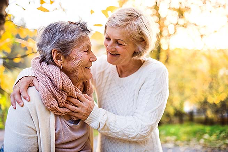 elderly women lovingly embracing one another