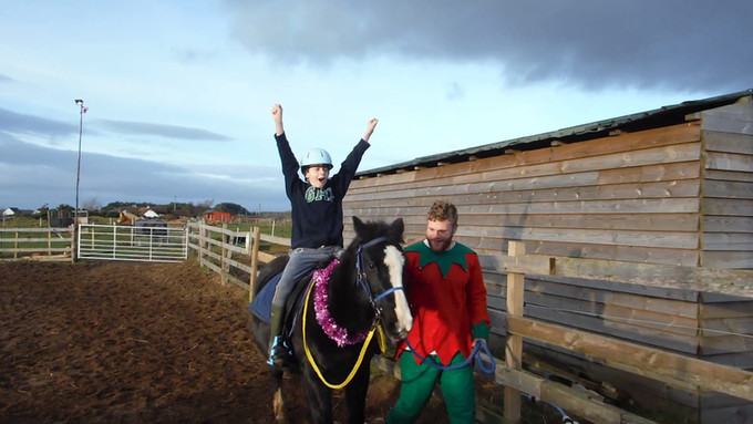 Benji riding Connie at the christmas party