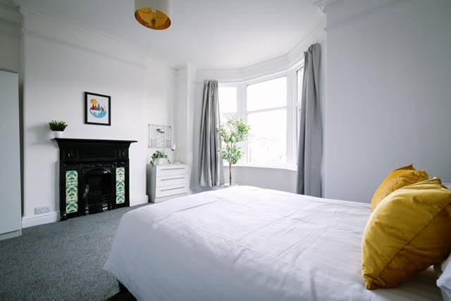white bedroom grey carpet feature fireplace