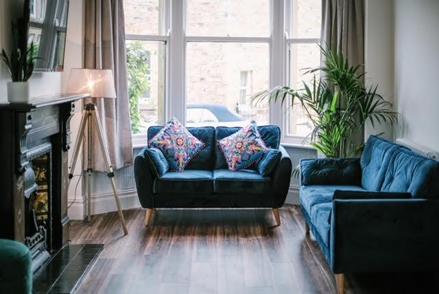 period fireplace blue velvet sofa bay window living room