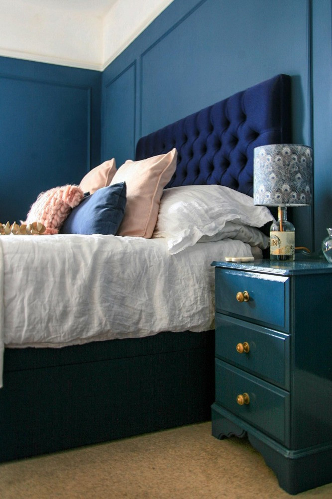 blue bedroom wood paneled walls button studded headboard