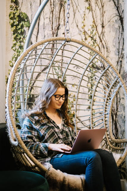 student on laptop sat in hanging rattan chair