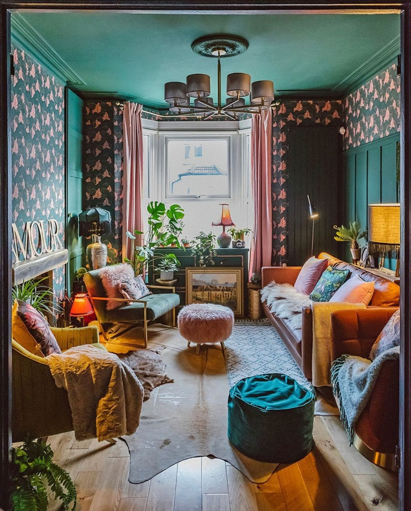 green living room pink curtain pink floral wallpaper wooden floor armchair poof footstool leather sofa bold interiors eclectic style