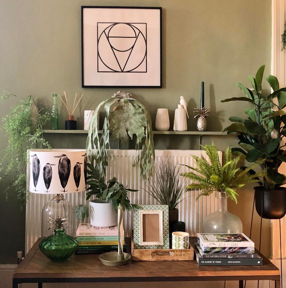 abigail ahern faux plants coffee table books photo frames heron lamp
