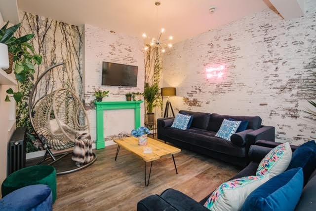 living room velvet sofa hanging rattan chair feature wallpaper neon sigh