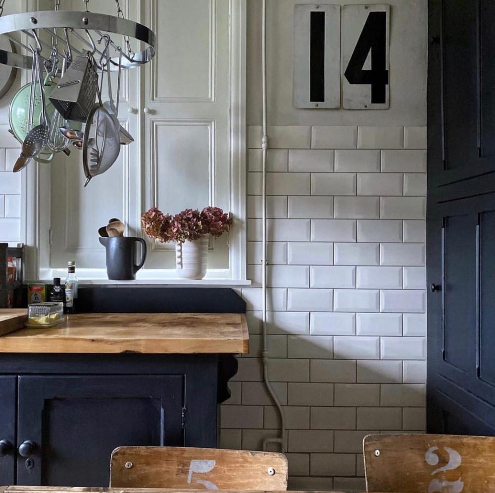 vintage kitchen style dark cabinets wooden table vintage school chairs roberts radio vintage numbers