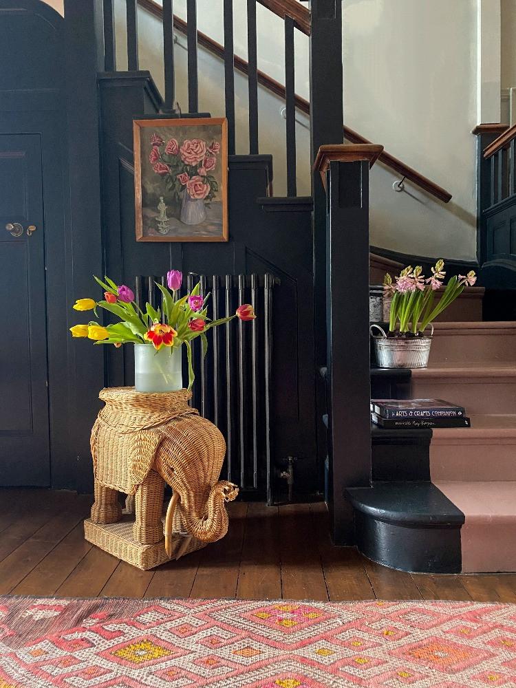 hallway dark painted stairs vintage paintings colourful rug tulips