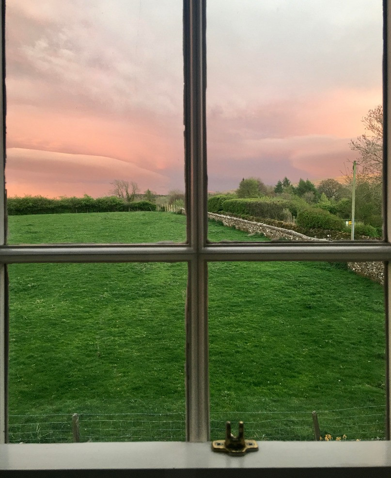 sunset view pink sky and green pasture