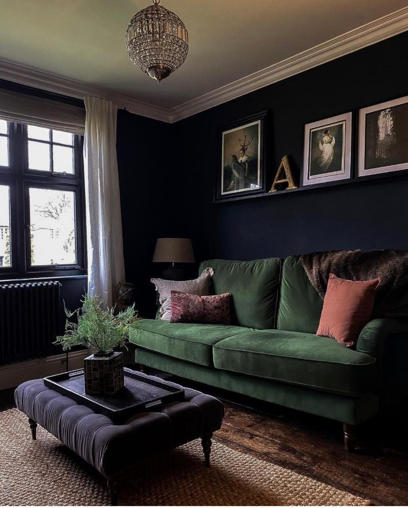 dark sitting room decor green velvet sofa button upholstery footstool picture shelf black windows crystal chandelier