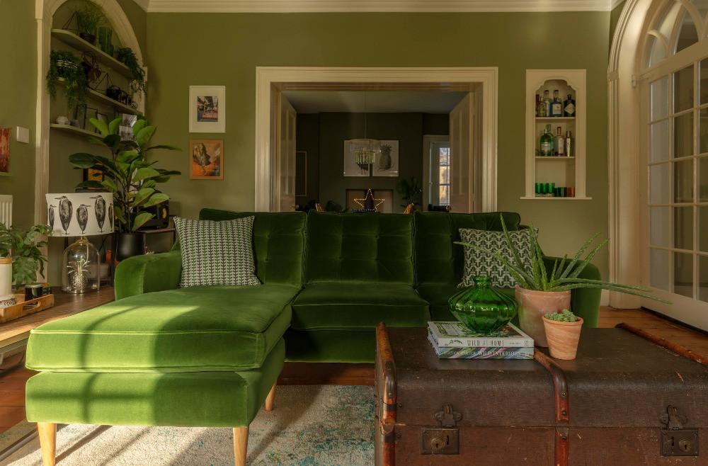 green velvet mid-century style sofa green walls vintage trunk Victorian house