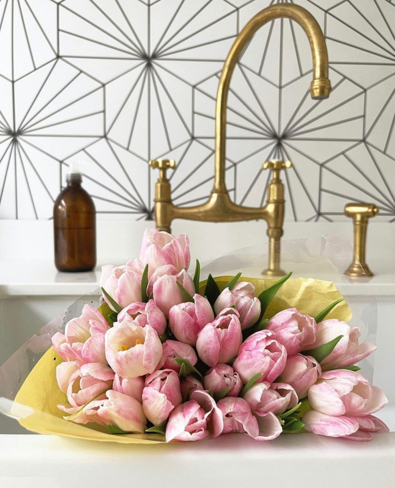 pink tulips in sink lilypad tiles gold tap