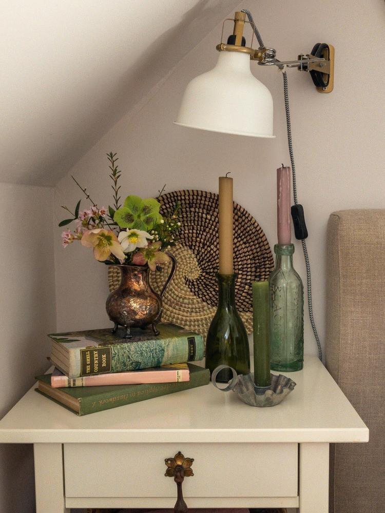 bedside vignette vintage books old bottle candlesticks wall lightt