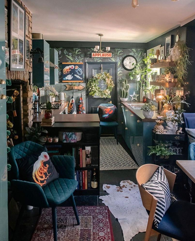 green maximalist kitchen diner floral wallpaper neon signs velvet chairs
