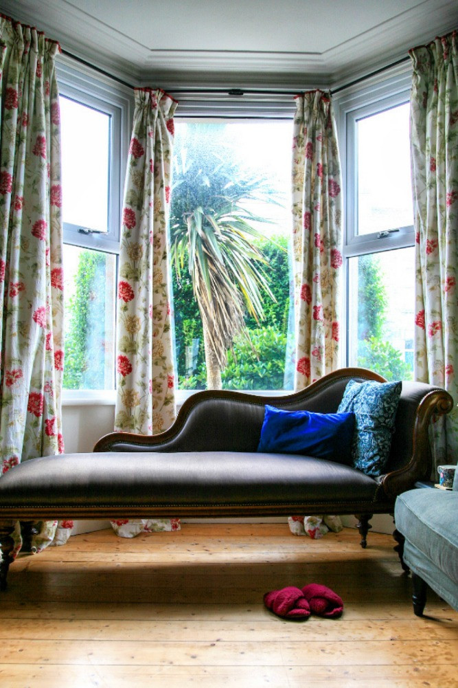 bay window chaise lounge wooden floor floral curtains