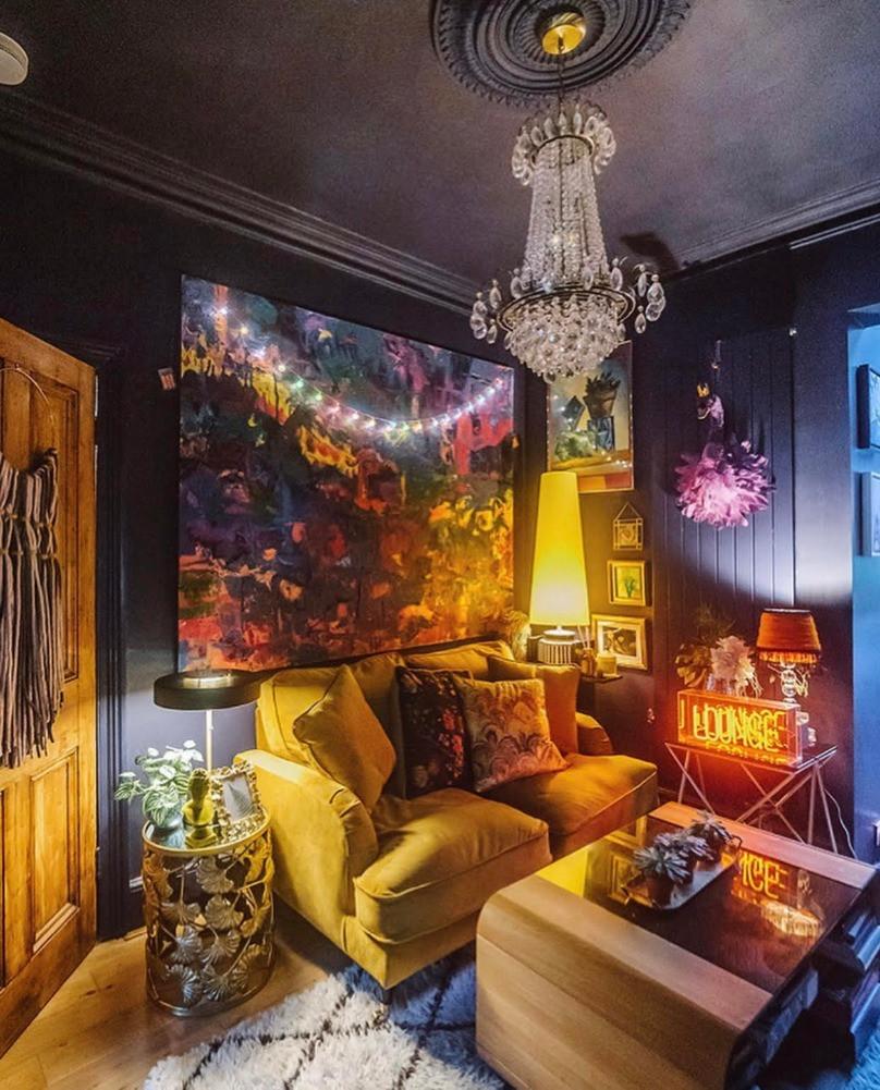 railings dark sitting room large abstract art chandelier yellow sofa ikat berber rug