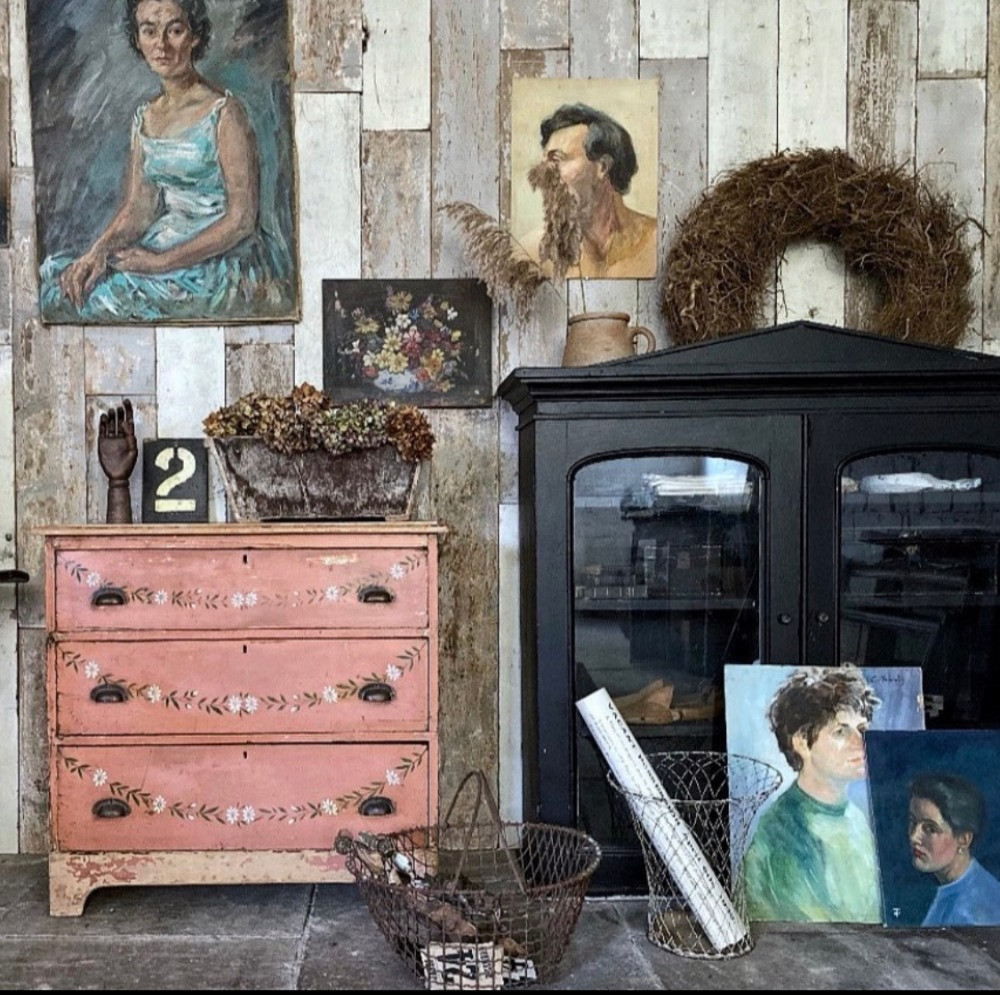 coral pink chest of vintage drawers wood paneled wall vintage portraits antique oil paintings
