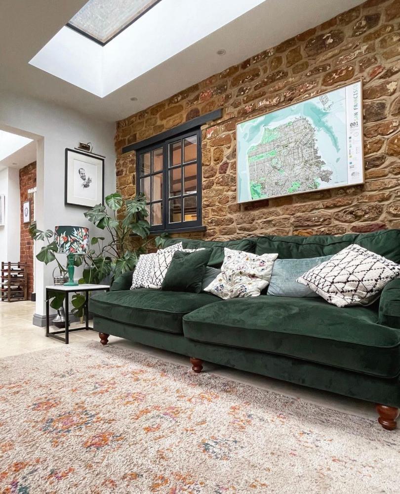 green velvet sofa map artwork exposed brick wall
