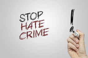 Hand writing stop hate crime on grey bac