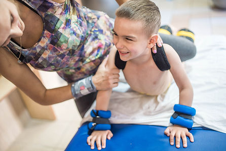 Little boy with cerebral palsy has musculoskeletal therapy by doing exercises. Child and t