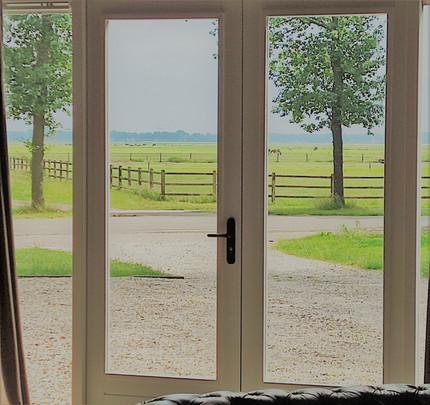 Uitzicht vanuit woonkamer op weilanden