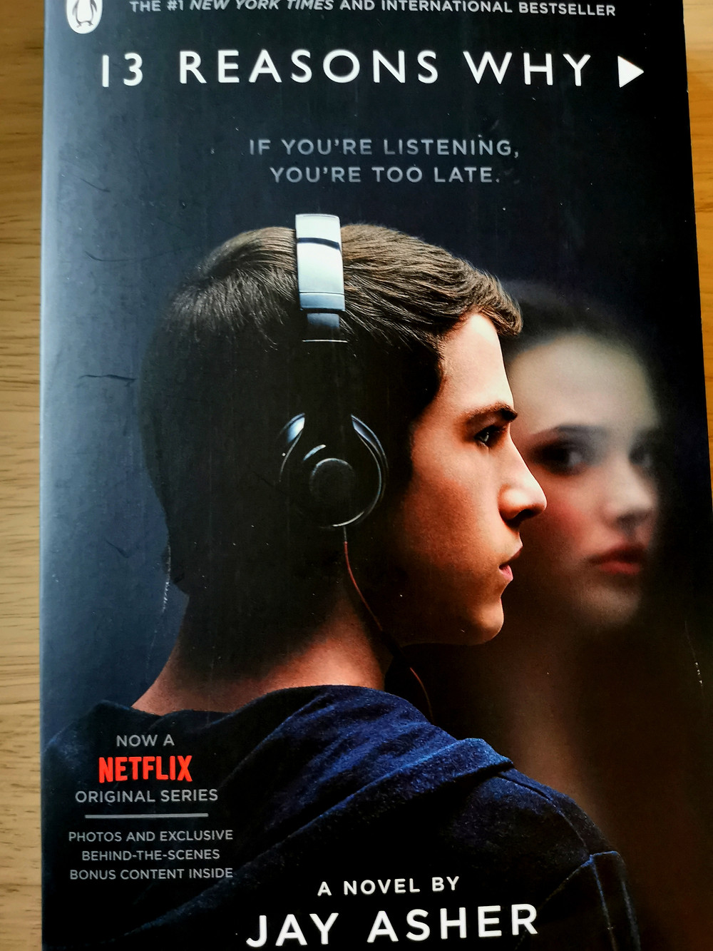 Cover photo of Jay Asher's 'Thirteen Reasons Why' with the actors from the TV series, showing Clay with headphones on and Hannah a ghost in the background