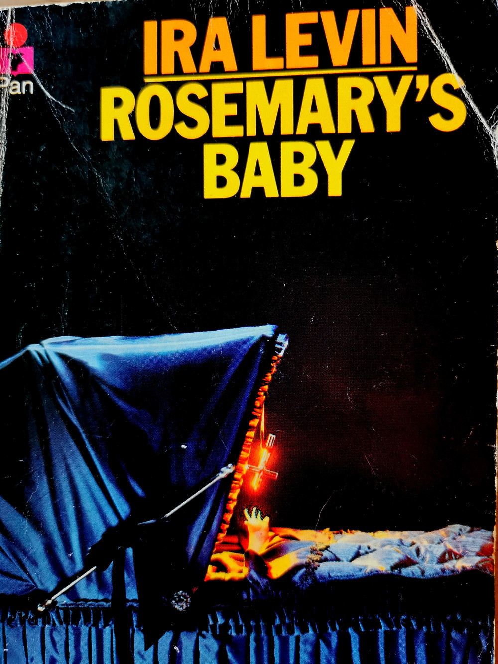 Cover photo of Ira Levin's 'Rosemary's Baby' featuring a baby in a bassinet reaching for an inverted flaming crucifix