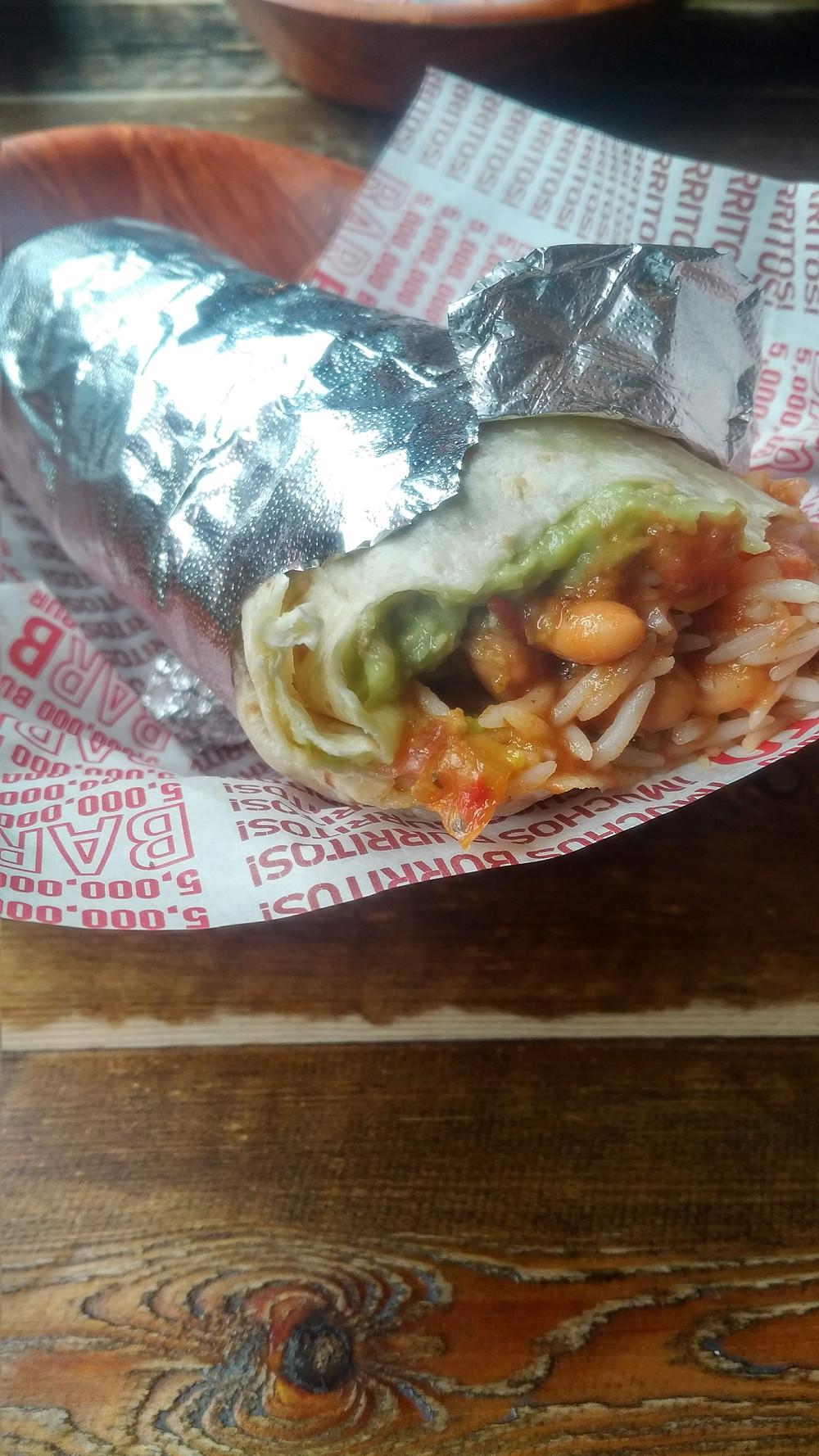 A vegan burrito wrapped in foil from Bar Burrito