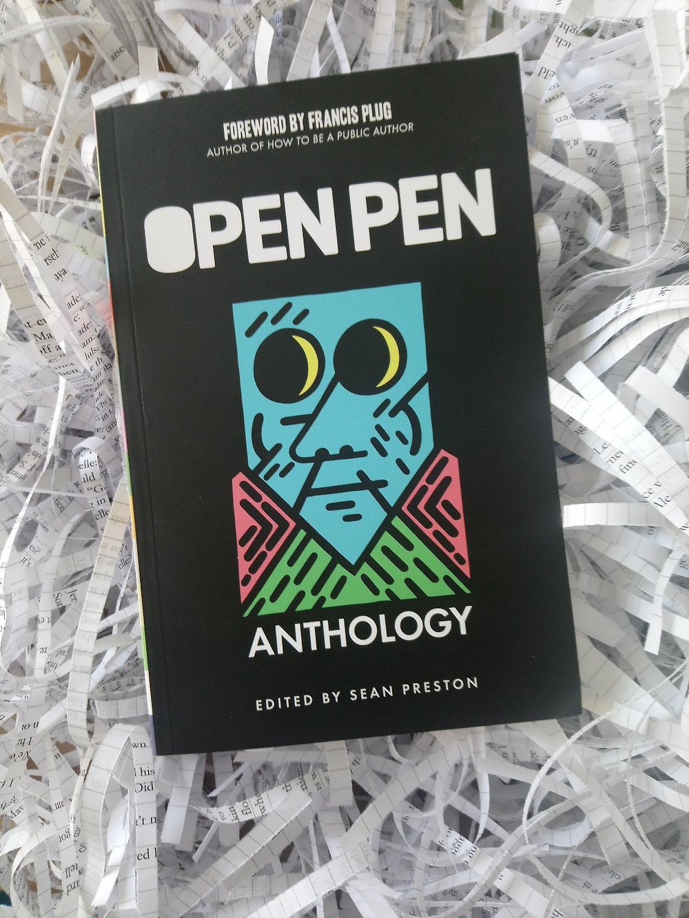 'Open Pen Anthology' edited by Sean Preston, a black cover showing multi-coloured shapes making up a face, on a bed of shredded paper