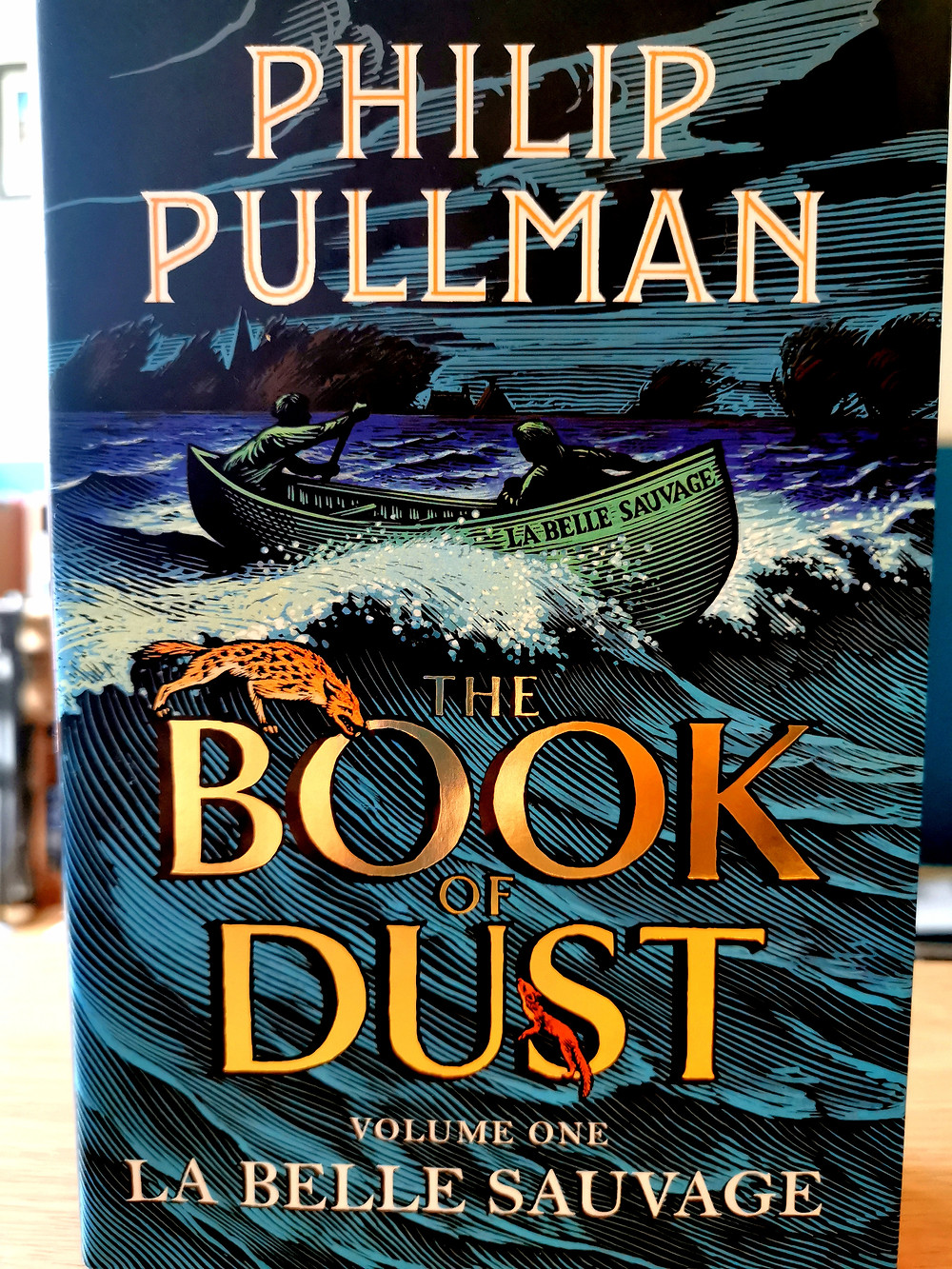 Cover photo of Philip Pullman's 'The Book of Dust Volume 1: La Belle Sauvage', showing a small boat on rough waves and two daemons - a hyaena and a weasel - clambering on the title