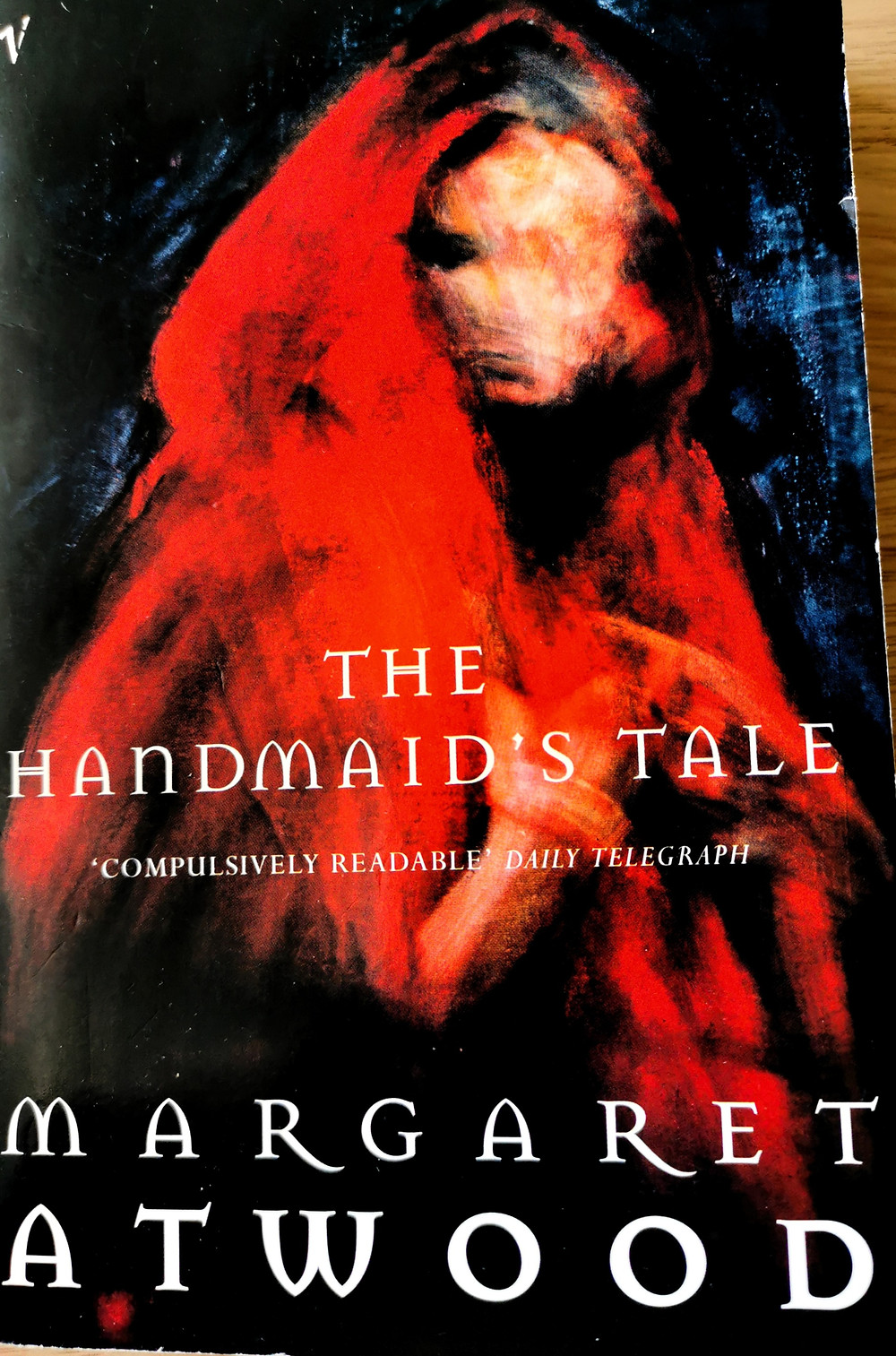 cover of Margaret Atwood's 'The Handmaid's Tale', showing an abstract painting of a faceless woman wrapped in a red cloak